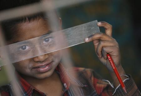 Un neno da India con VIH ledo co seu lapis na escola.