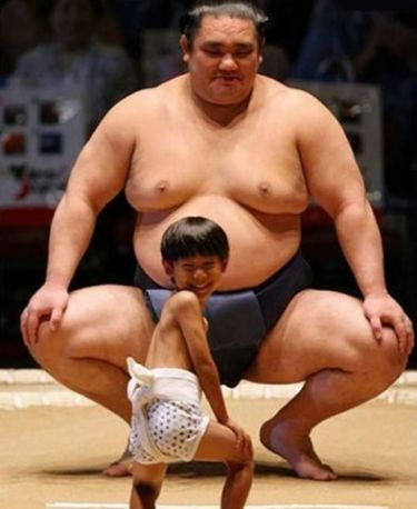 Imaxe: dous loitadores de sumo, un profesional como unha mole e un raparigo miúdo pequerrecho.