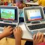 Dous portatiles magalhaes nunha mesa da aula cos rapaces